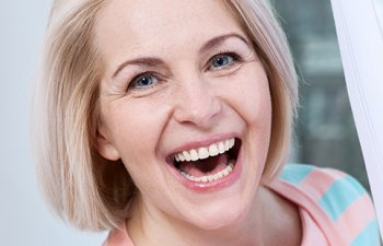 senior woman with dental implants smiling